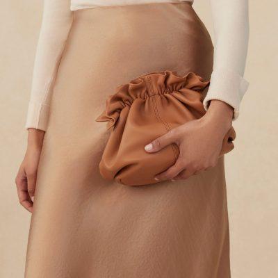 model holding tan leather clutch bag by loeffler randall